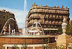 Place de la Préfecture, les Jets d'eau  et, au fond, l'Arc de Triomphe élevé en l'honneur de Louis X